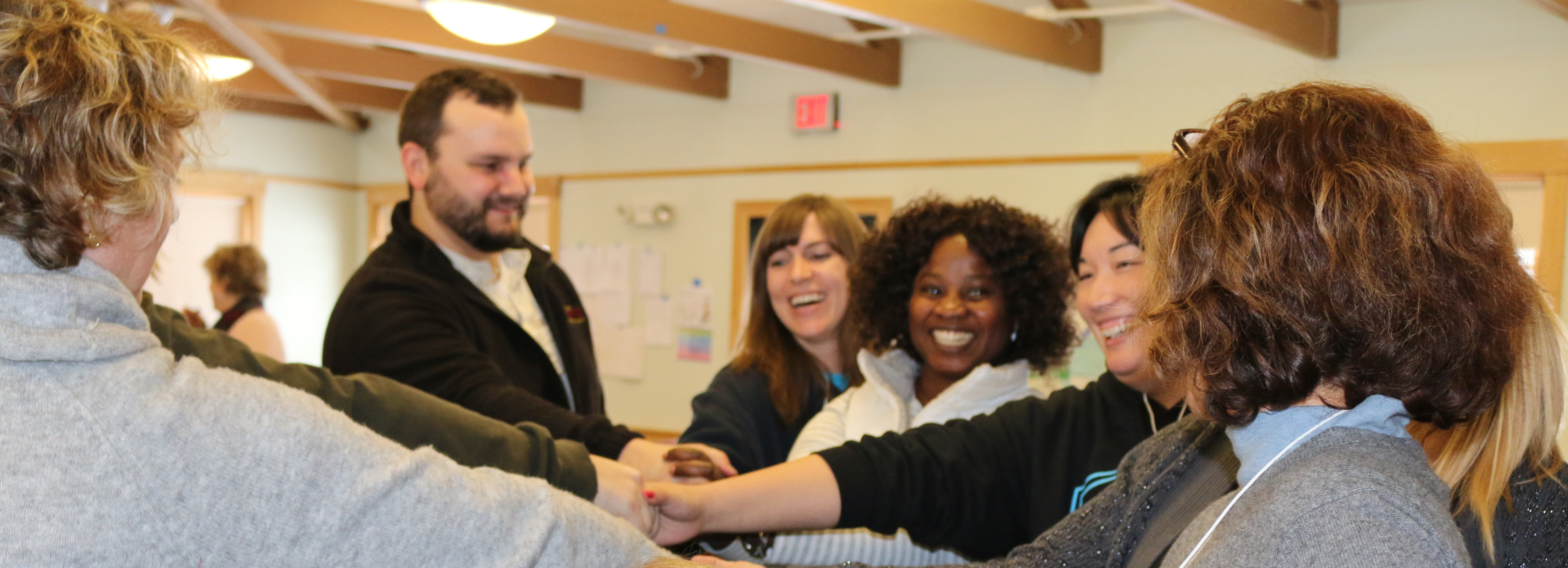 NH Leadership Series graduates gather in a circle with their hands centered in anticipation of a group cheer..
