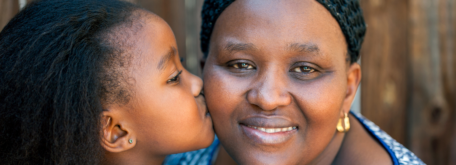 A child kisses her mother on the cheek