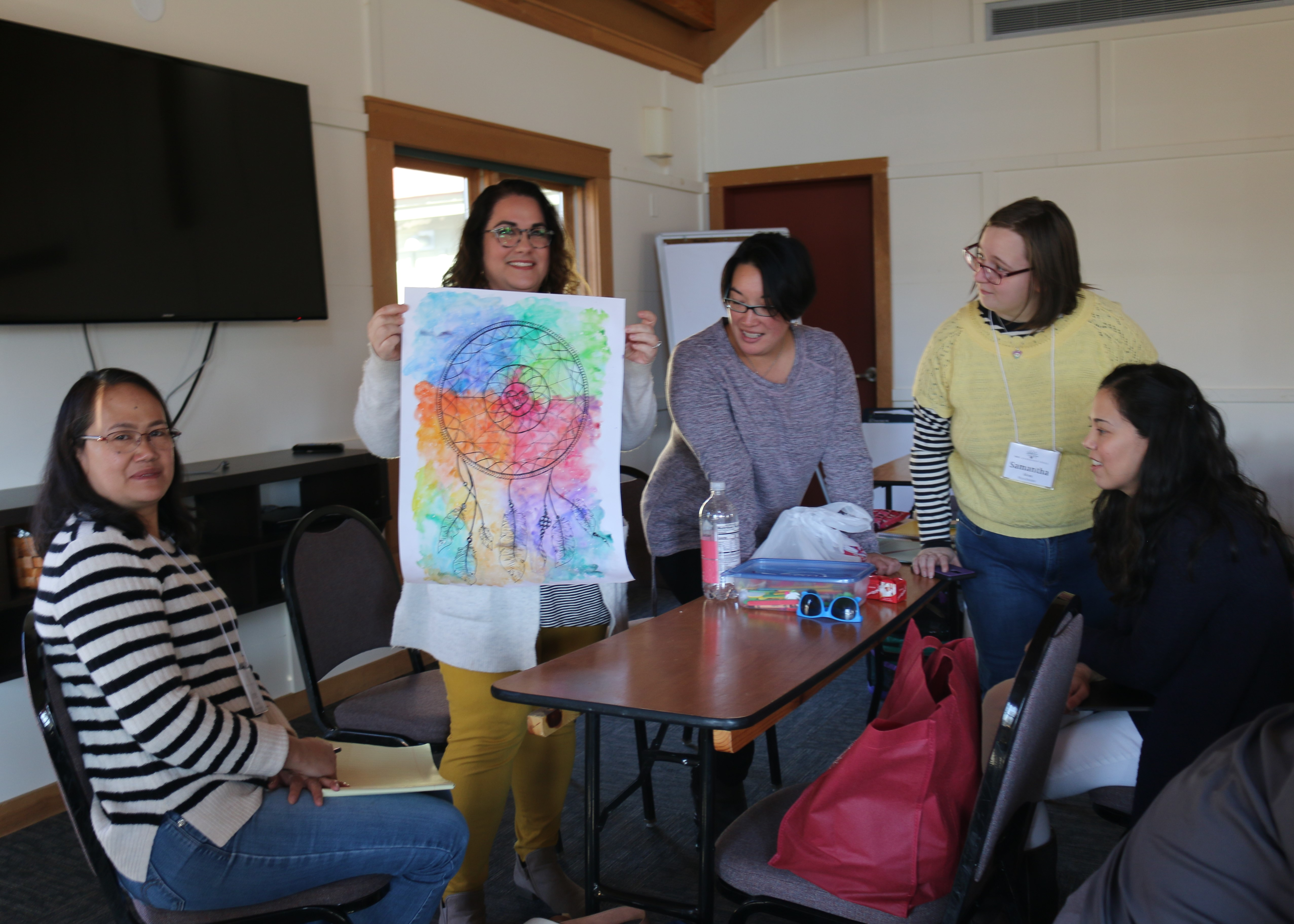 5 Leadership participants around a table looking at a piece of art that has a drawing of a colorful dreamcatcher
