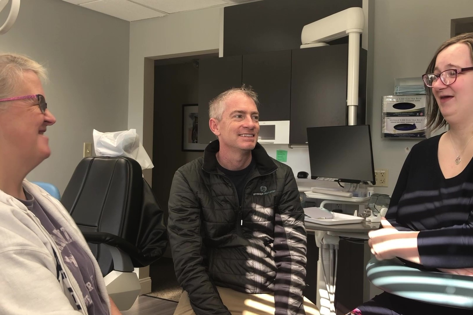 Three people in a dentists office having a conversation