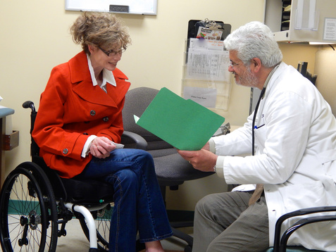 Woman using a wheelchair talks to her doctor in an exam room