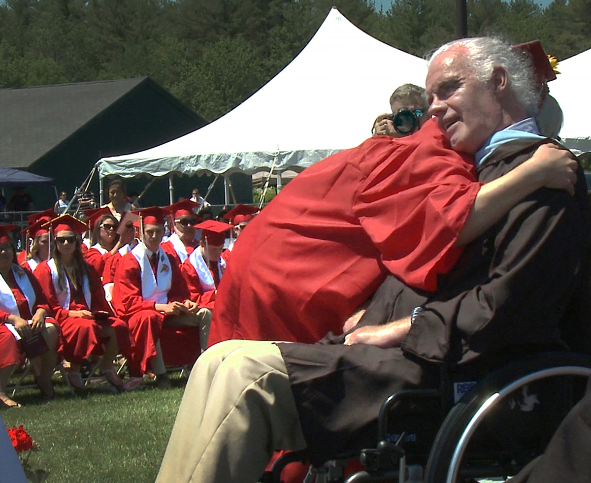 child hugging a man (gene connolly) in a wheel chair